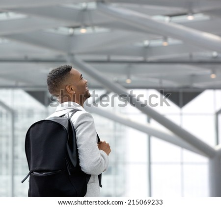 Portrait from behind of a young black man at airport with bag - stock photo