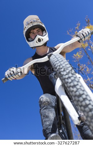 portrait from below of a young man BMX biker sitting on his bike on a BMX circuit in the mountain - focus on the face - stock photo