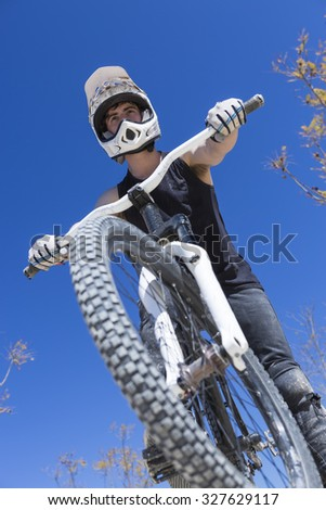 portrait from below of a young man BMX rider sitting on his bike on a BMX circuit in the mountain - focus on the face - stock photo