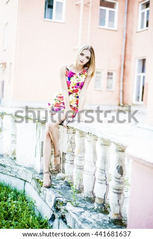 Portrait full length of Beautiful young adult slim caucasian woman stand against abandoned old fence. blond cute girl wear short fashion colorful dress with flowers pattern.  - stock photo