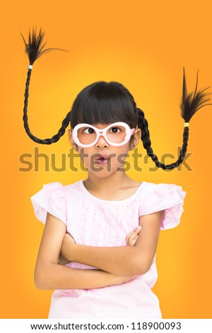 Portrait funny asian little girl with pigtail hair, Orange background - stock photo
