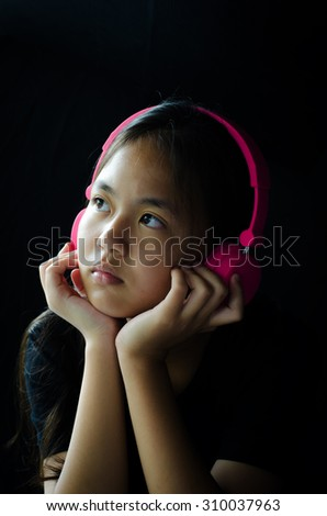 portrait Girl listening to music and feel sad. - stock photo