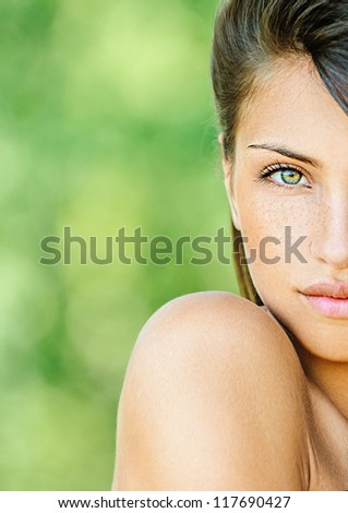 Portrait half of face young beautiful woman with bare shoulders , on green background summer nature. - stock photo