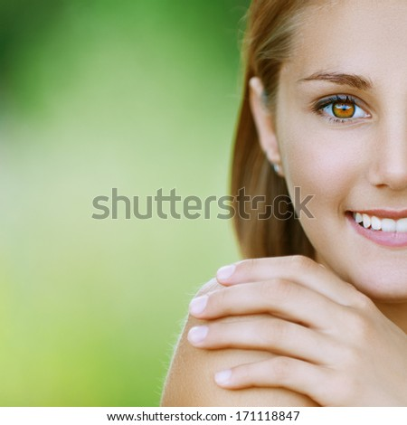 Portrait half of smiling beautiful young woman close up, against background of summer green park. - stock photo