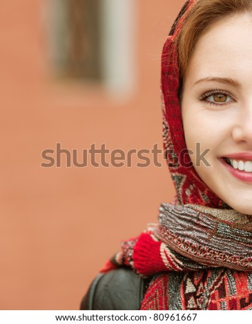 Portrait half of smiling charming young woman in headscarf on red background. - stock photo