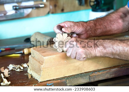 portrait hands of carpenter planing on a piece of wood at work in the workshop - stock photo