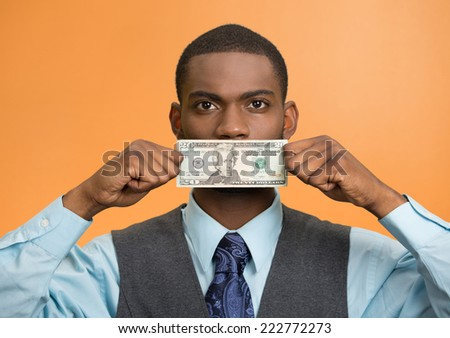 Portrait handsome corrupt guy businessman holding twenty dollar bill to mouth silent avoiding truth isolated orange background. Bribery concept in politics business diplomacy. Face expression attitude - stock photo