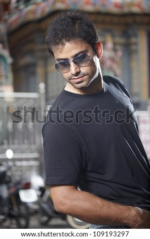Portrait handsome indian man in sunglasses at the street - stock photo