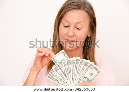 Portrait happy attractive mature woman presenting US dollar notes, isolated, bright background. - stock photo