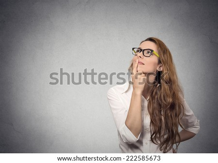 Portrait happy beautiful woman thinking looking up isolated grey wall background with copy space. Human face expressions, emotions, feelings, body language, perception  - stock photo