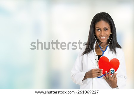 Portrait happy confident African American female doctor medical professional holding red heart listening with stethoscope isolated on hospital hallway windows background. Positive face expression  - stock photo
