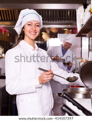 portrait happy female cook cooking at professional kitchen in the take-away  restaurant - stock photo