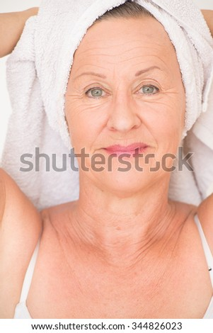 Portrait happy healthy attractive senior woman with white spa towel on head, bright background. - stock photo