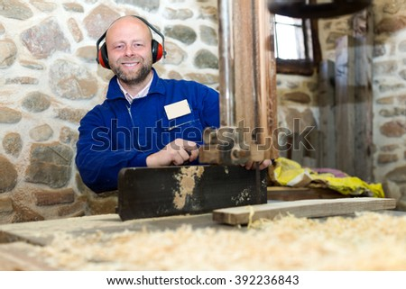 portrait happy male worker on lathe at  wood workroom - stock photo