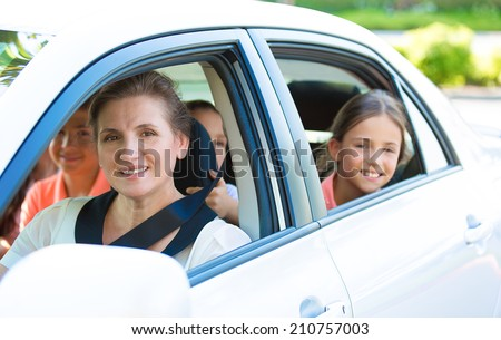 Portrait happy, smiling Family, mother, three kids sitting in the white, silver car looking out windows, ready for vacation trip, outdoor background. Positive Human face expression, emotions, feelings - stock photo