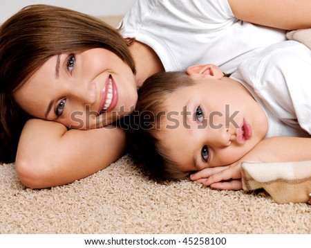 Portrait happy smiling  mother and the child lying on a floor in the apartment - stock photo