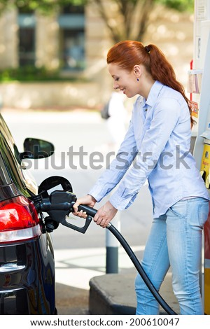 Portrait happy smiling pretty, attractive woman filling compact car tank with petrol at gas station isolated city background. Oil prices economy, energy cost, transportation industry, travel, concept  - stock photo