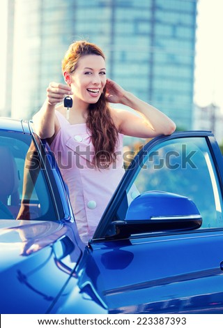 Portrait happy smiling young attractive woman buyer standing next to new blue car showing keys isolated outside dealer, dealership lot corporate office. Personal transportation auto purchase concept - stock photo