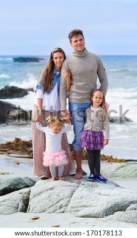portrait happy young family of four in casual fashion wear on a sandy beach at sunny summer day - stock photo