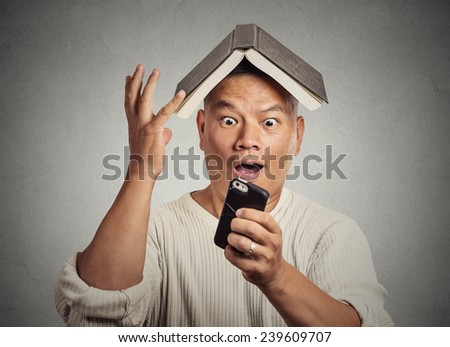 Portrait headshot surprised stunned middle aged man funny looking guy with book on head reading news on smart phone isolated grey wall background. Human face expression emotion reaction perception - stock photo