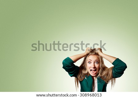 Portrait headshot very sad depressed, stressed disappointed gloomy young man head on hands screaming in despair isolated on pistachio wall background. Human emotion facial expression reaction - stock photo