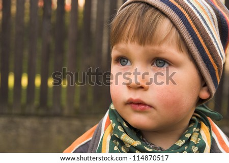 Portrait if the little boy wearing knitted cap, made in the fall in the garden - stock photo