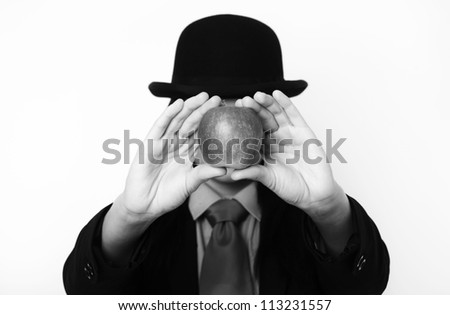 portrait image of sexy woman wearing a suit with bowler hat based around the painting of Rene Magritte - stock photo