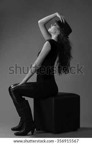 Portrait in black and white of a sexy brunette woman in edgy outfit posing on chair with a black fedora hat on her long hair. - stock photo