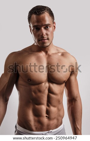 Portrait in studio of muscular male in black swimming trunks. Isolated on grey background. - stock photo