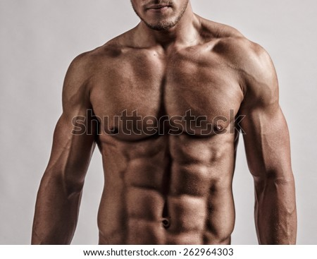 Portrait in studio of muscular malebody. Isolated on grey background. - stock photo