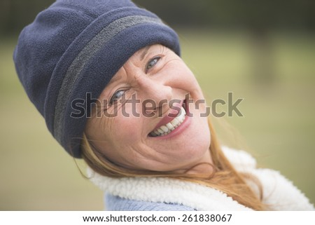 Portrait joyful confident attractive mature woman outdoor, wearing warm bonnet and wool jacket, blurred green background. - stock photo