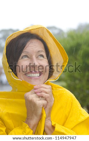 Portrait mature woman standing in the rain, wearing yellow raincoat, isolated with blurred background and copy space. - stock photo