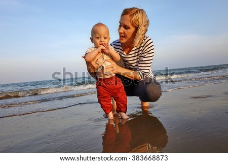Portrait mom with toddler boy at the sea beach in fun - stock photo