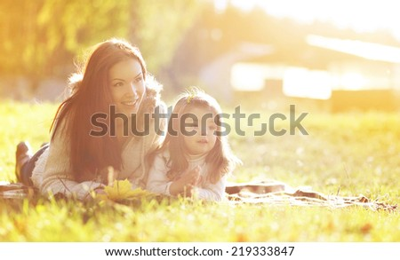 Portrait mother and child on the grass in autumn day - stock photo