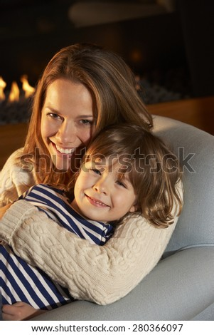 Portrait mother and son sitting in front of fire - stock photo