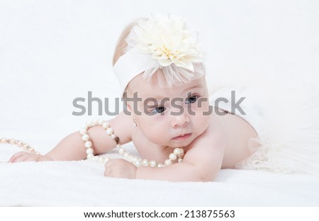Portrait newborn baby lying in bed with a pearl necklace  - stock photo