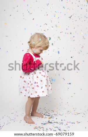 Portrait od cute girl with colorful confetti having fun - stock photo
