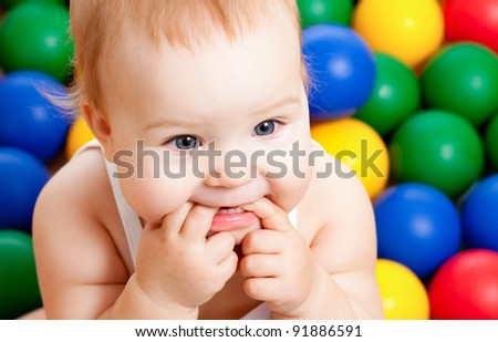 Portrait of a adorable infant sitting among colorful balls - stock photo