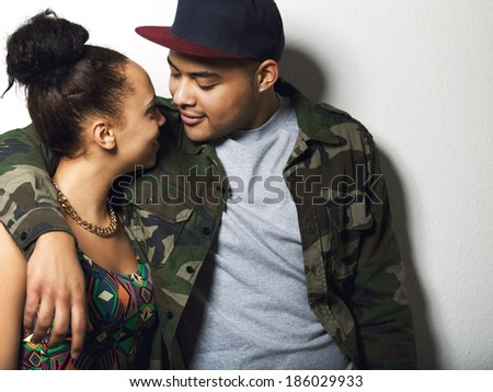 Portrait of a affectionate young couple together looking at each other on grey background. Young man and woman in love. - stock photo