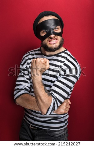 Portrait of a angry bandit threaten with a fist on red background  - stock photo