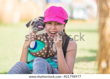Portrait of a asian teenage woman girl hug and play with her cute dog puppy pug outdoors on fields - stock photo