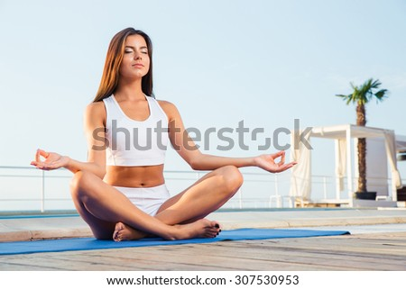 Portrait of a attractive girl meditating outdoors  - stock photo