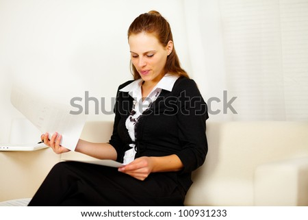 Portrait of a attractive woman smiling and working with a laptop and documents - stock photo