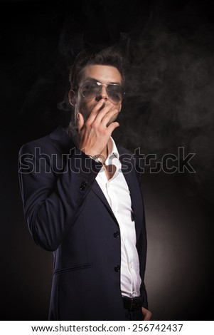 Portrait of a attractive young business man smoking o cigarette on black background. - stock photo