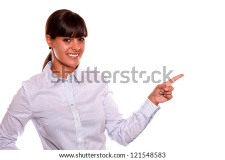 Portrait of a attractive young business woman pointing to her left up while is looking at you standing over white background - copyspace - stock photo