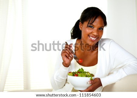 Portrait of a attractive young woman smiling and eating a vegetable salad and looking at you on a light background. With copyspace. - stock photo