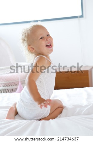 Portrait of a baby girl laughing and playing in bed - stock photo