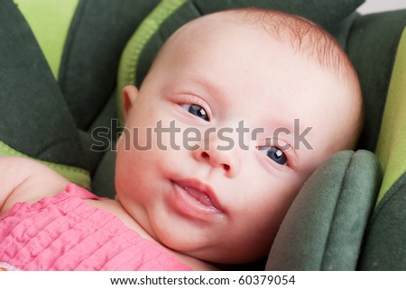 Portrait of a baby girl toddler lying comfortable in car seat - stock photo
