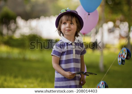 Portrait of a baby in a hat near the air balls, park - stock photo
