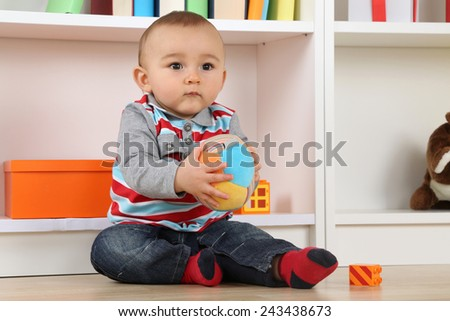 Portrait of a baby playing with a ball in children's room - stock photo